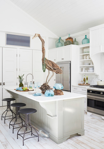 Wooden bird sculpture on dining table in kitchen at cottageの写真素材 [FYI03691743]