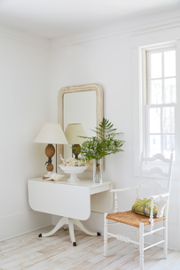 Decorated table and mirror by window in beach cottageの写真素材 [FYI03691746]