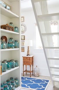 Mason jars arranged on shelves in living room at cottageの写真素材 [FYI03691748]
