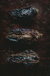 Overhead view of dried ancho chili pepper on wooden tableの写真素材 [FYI03691773]