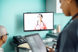 Happy female doctor video conferencing with colleague and patient in clinicの写真素材 [FYI03691908]