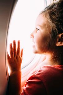 Curious girl looking through airplane windowの写真素材 [FYI03692073]