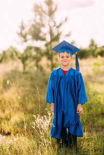 Portrait of happy boy in graduation gown standing on fieldの写真素材 [FYI03692121]