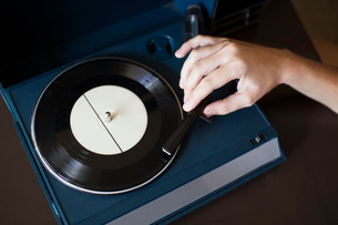 Cropped image of woman playing record player on tableの写真素材 [FYI03692417]
