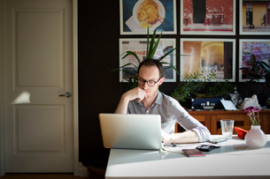 Mid adult man using laptop at homeの写真素材 [FYI03692477]