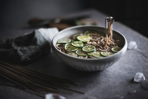 Close-up of soba noodles in bowl with chopsticks on kitchen counterの写真素材 [FYI03692724]