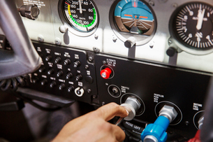 Cropped image of pilot operating control panel in airplaneの写真素材 [FYI03692998]