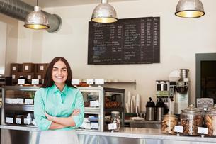 Portrait of happy owner standing in coffee shopの写真素材 [FYI03693333]