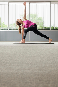 Woman practicing triangle position in gymの写真素材 [FYI03693367]