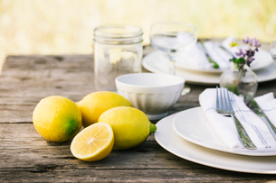 Close-up of lemons by plates on tableの写真素材 [FYI03693551]