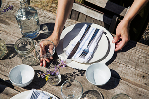 Cropped image of hands arranging crockery on tableの写真素材 [FYI03693554]