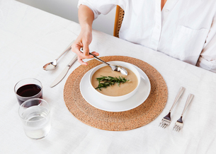 High angle view of woman dipping spoon in soup at dining tableの写真素材 [FYI03693574]