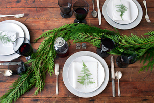 Overhead view of crockery with red wine and leaves on dining tableの写真素材 [FYI03693592]
