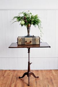Metallic vase on suitcase against wallの写真素材 [FYI03693601]