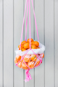 Bunch of fresh oranges in rope basket hanging against wooden wallの写真素材 [FYI03693651]