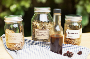Jars of spices with syrup bottle and cloth on wooden tableの写真素材 [FYI03693655]