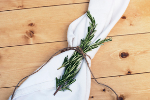 Overhead view of rosemary and napkin on wooden tableの写真素材 [FYI03693662]