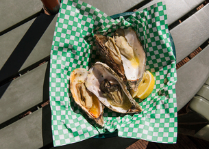 Overhead view of oyster shells and lemon in plate on tableの写真素材 [FYI03693700]