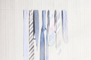 Neckties hanging on clothesline against wooden wallの写真素材 [FYI03693720]