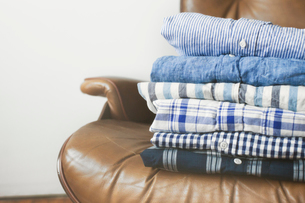 Folded shirts stacked on armchair at homeの写真素材 [FYI03693732]