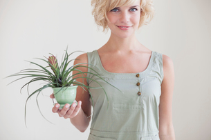 Portrait of beautiful woman holding potted plant against wallの写真素材 [FYI03693883]