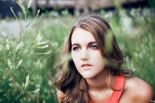 Thoughtful woman looking away while sitting on grassy fieldの写真素材 [FYI03694000]