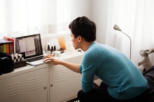 Side view of man using laptop in bedroomの写真素材 [FYI03694091]