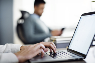 Cropped image of businessman using laptop in creative officeの写真素材 [FYI03694363]