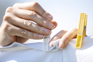 Close-up of woman putting clothespin on clothesの写真素材 [FYI03694399]