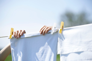 Close-up of woman drying clothes on clotheslineの写真素材 [FYI03694401]