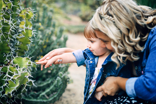 Mother assisting curious girl in touching cactus thornの写真素材 [FYI03694852]