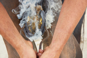 Midsection of farrier putting shoe on horseの写真素材 [FYI03695041]