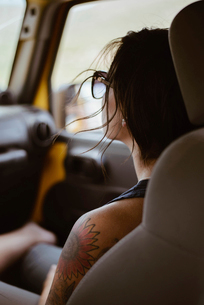 Young woman with tattoo on shoulder sitting in off-road vehicleの写真素材 [FYI03695171]
