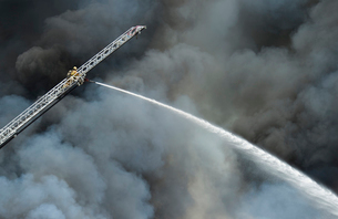 Low angle view of firefighter on crane spraying water over gray smokeの写真素材 [FYI03695511]
