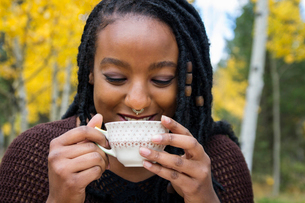 Happy woman drinking tea against trees in backyardの写真素材 [FYI03696157]