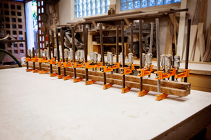 Row bar clamps holding wooden planks on table at workshopの写真素材 [FYI03696431]