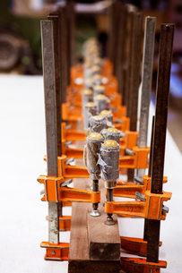 High angle view of bar clamps holding wooden planks on table at workshopの写真素材 [FYI03696432]