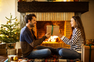 Happy couple holding Christmas present by fireplace at homeの写真素材 [FYI03696557]