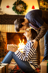 Romantic couple with Christmas present rubbing noses at homeの写真素材 [FYI03696560]
