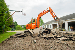 Man in earth mover digging land at construction siteの写真素材 [FYI03696675]