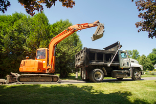 Earth mover and truck on grassy fieldの写真素材 [FYI03696681]