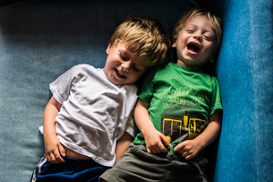 High angle view of happy brothers lying on sofa at homeの写真素材 [FYI03696766]