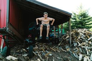 Full length of boy sitting on equipment in warehouseの写真素材 [FYI03696840]