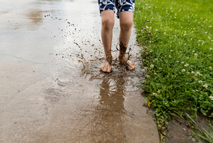 Low section of boy jumping in dirty puddleの写真素材 [FYI03696888]