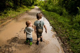 Rear view of messy brothers walking in dirty puddle on roadの写真素材 [FYI03696907]