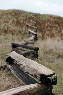 Wooden railing on grassy fieldの写真素材 [FYI03696932]