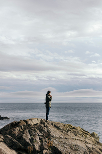 Side view of man standing on rock formation by sea against cloudy skyの写真素材 [FYI03696940]