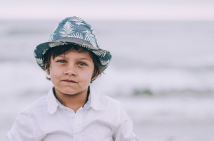 Portrait of boy standing at beach against skyの写真素材 [FYI03696953]