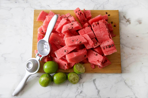High angle view of chopped watermelon and lemons on cutting board with squeezerの写真素材 [FYI03697197]