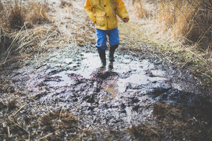Low section of boy walking in dirty puddleの写真素材 [FYI03697236]